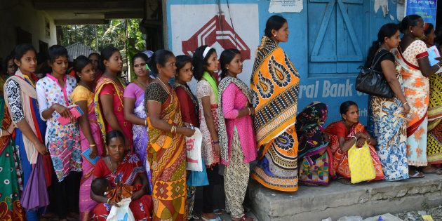 Indian village customers form queues outside banks to deposit and exchange old denomination Indian Rupee...