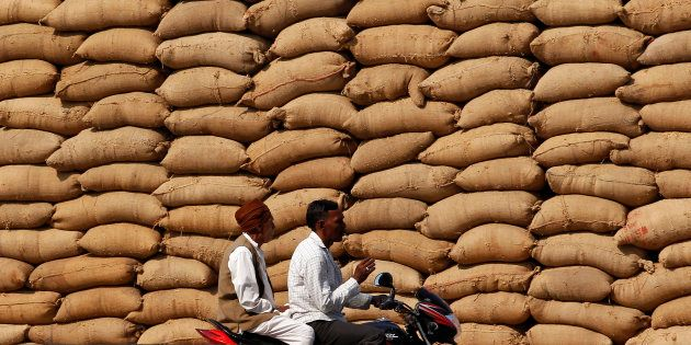 Farmers ride on a motorbike in front of stacked sacks filled with grains at the Agricultural Produce...