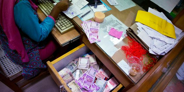 A bank employee counts discontinued currency notes while working at a currency exchange counter at a...