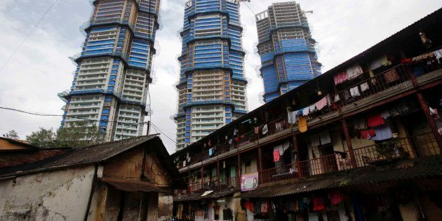 High-rise residential towers under construction are pictured behind an old residential building in central