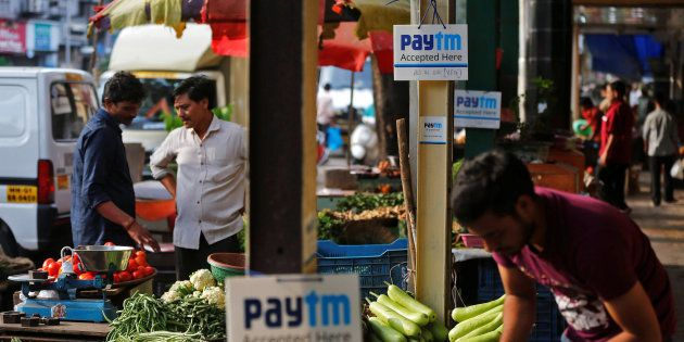 Advertisement boards of Paytm, a digital wallet company, are seen placed at stalls of roadside vegetable...