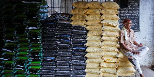 A labourer sits on sacks of food grains while waiting for customers at a wholesale market in
