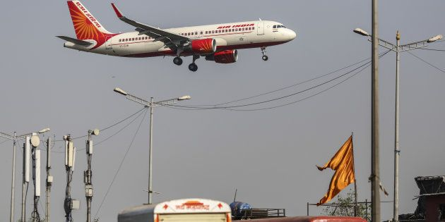 An Air India Ltd. aircraft passes over traffic as it prepares to land at Chhatrapati Shivaji International...