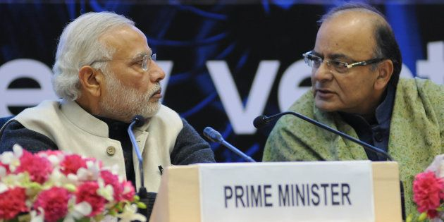 Prime Minister Narendra Modi and Finance Minister Arun Jaitley talk during an event to launch an initiative...