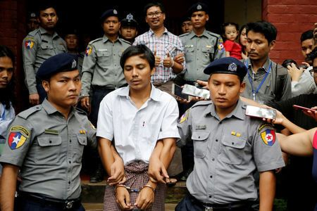 Reuters reporters Wa Lone and Kyaw Soe Oo, shown handcuffed in the center above, have been imprisoned for more than a year no