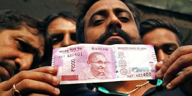A man displays a new 2000 Indian rupee banknote after withdrawing from a