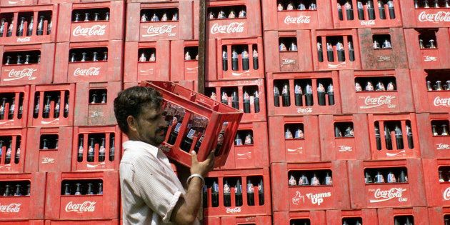 A worker carries a crate of Coca Cola at the local dealer in