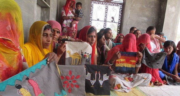 Women embroiders show their latest work after a training
