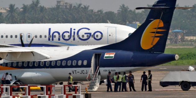 Airport staff stand next to parked passenger jets of IndiGo and Jet