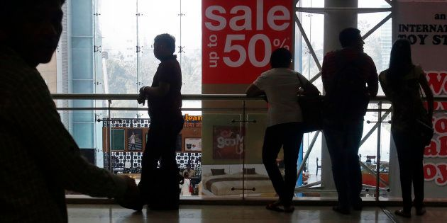 Representative image. Shoppers are silhouetted as they stand near a sign advertising a sale at a shopping...