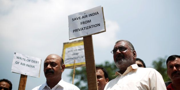 Air India employees hold placards as they shout slogans during a protest against the proposed privatisation...