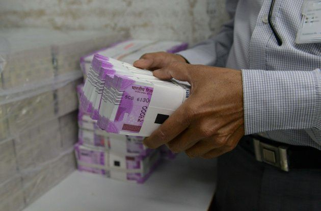 An Indian bank employee checks stacks of new 2000 rupee notes in Ahmedabad on November 11,