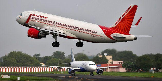 An Air India aircraft takes off as an IndiGo Airlines aircraft waits for clearance at the Sardar Vallabhbhai...