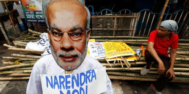 A supporter of Congress party sits next to an effigy of Indian Prime Minister Narendra Modi during a...