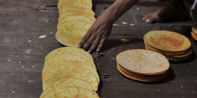 An Indian worker arranges khakra at a food