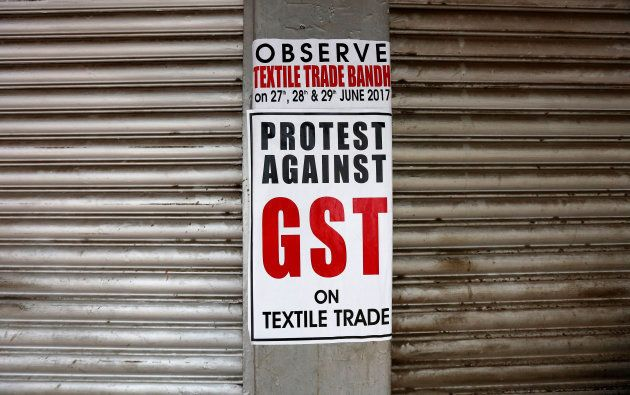 A poster is pictured on closed garment shops during a protest against implementation of Goods and Services...
