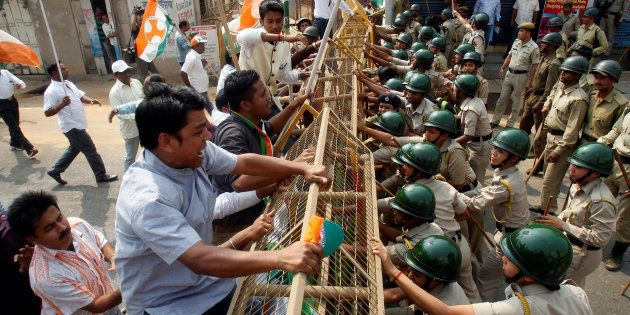 Demonstrators try to cross a police barricade during a protest organized by India's main opposition Congress...