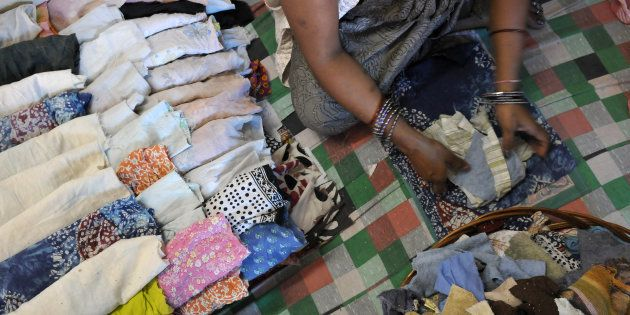 A woman worker making recyclable sanitary cloth napkins at the processing unit of NGO Goonj at Madanpur...