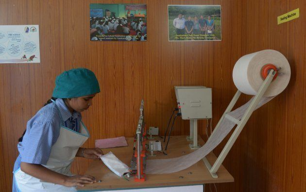 In this photograph taken on September 22, 2014, an Indian schoolgirl makes sanitary napkins at a school...