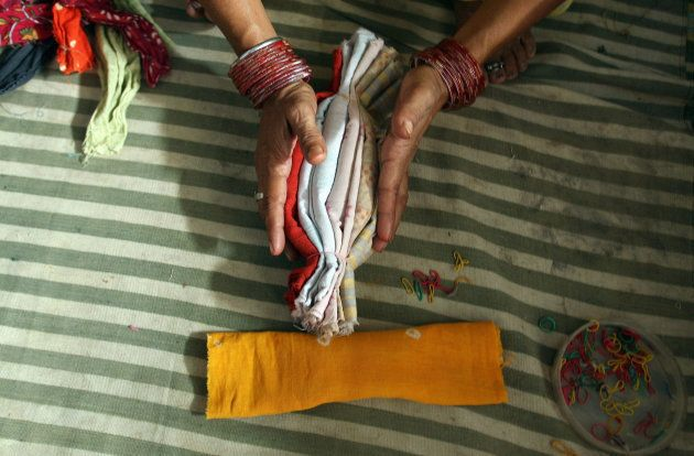 Indian woman makes cloth sanitary napkins at the NGO Goonj in New Delhi, 10 September
