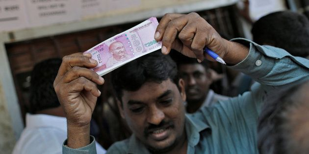 A man holds 2000 Indian rupees notes as he gets out of a bank in Mumbai, India, November 24, 2016. REUTERS/Danish