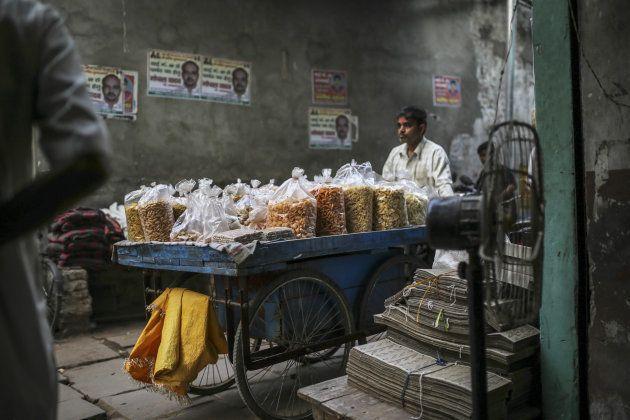 A snack vendor pushes a food cart on a street in Varanasi, Uttar Pradesh, India, on Saturday, Oct. 29,