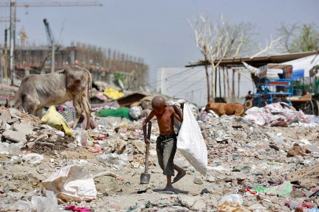 A boy looks for scrap metal near a construction site in New