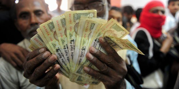 A file photo of a man holds up old versions of the Rs 500 notes as people queue inside a bank to deposit...