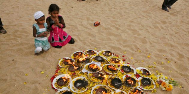 Young Indian kids offer prayers at Marina beach, that was hit by the 2004 tsunami, in Chennai, India, Wednesday, Dec. 26, 2012. The Dec. 26, 2004 tsunami killed an estimated 230,000 people in 12 Indian Ocean nations, from Thailand to Sri Lanka. (AP Photo/Arun Sankar K.)
