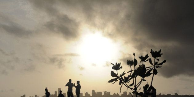 Indians stroll near the seafront as dark clouds gather over city skyline in Mumbai on June 27, 2012....