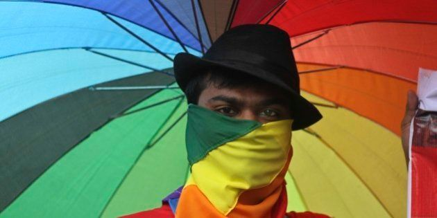 A participant holds an umbrella with rainbow colors as members of the Lesbian, Gay, Bisexual, Transgender...