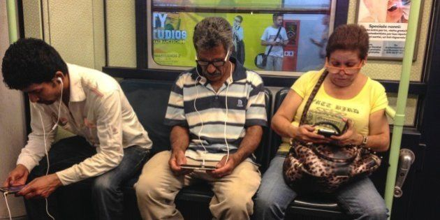 Three commuters comfortably Seated in the subway train Busy working on their electronic device. Milano,