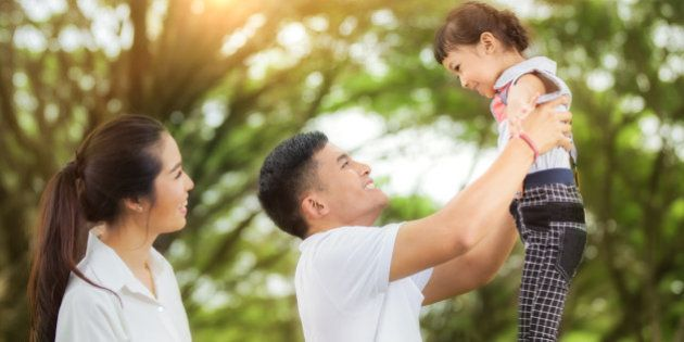 happy asian young family spending time outdoor on a summer