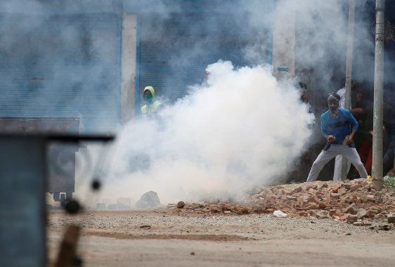 Protesters throw stones amid tear gas smoke fired by Indian police during a protest against the killing...