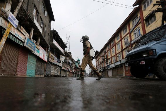 An Indian policeman wearing riot gear patrols on a deserted road during a curfew in Srinagar, July 10,...