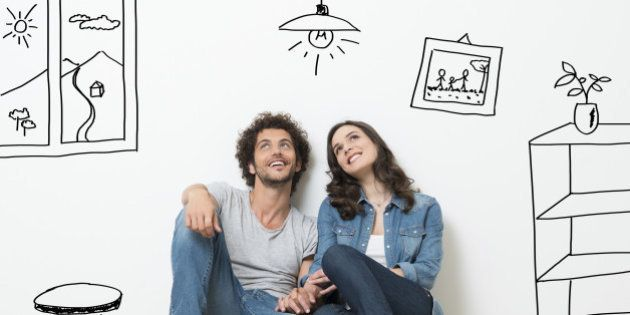 Portrait Of Happy Young Couple Sitting On Floor Looking Up While Dreaming Their New Home And