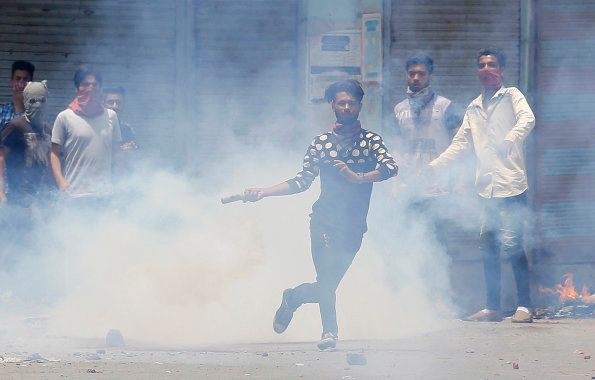 A Kashmiri Muslim protester throws back a teargas shell at Indian paramilitary soldiers in Srinagar,...