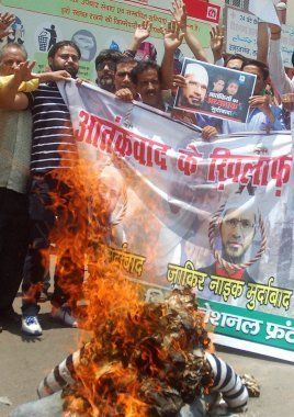 Lucknow: Activists of Shia National Front burning the effigy of Islamic preacher Zakir Naik against his...