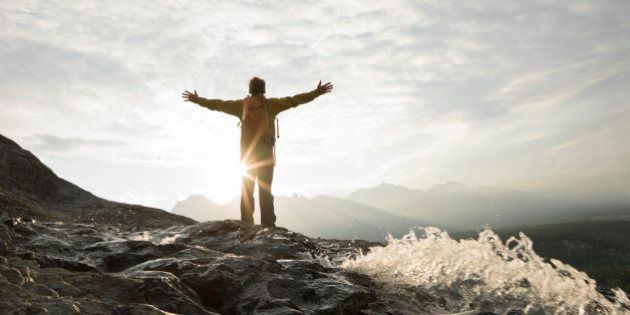 Man raises arms to sunrise over mountains,