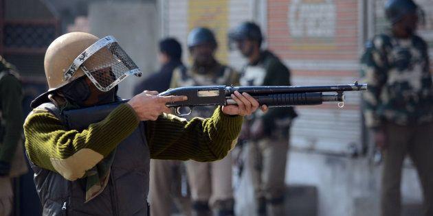 SRINAGAR, JAMMU AND KASHMIR, INDIA - 2016/02/05: A policeman points a pellet gun at protesters during...