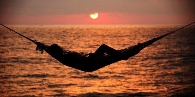 TRIVANDRUM, INDIA - JANUARY 12: A woman relaxes in a hammock at sunset on the beach of Varkala. on January...