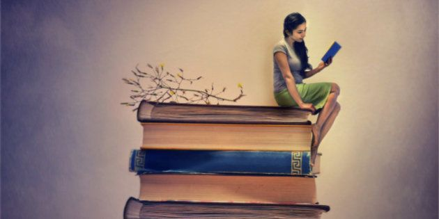 A girl sitting on a pile of book and also reading one. Miniature