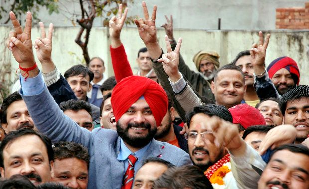 Former cricketer and politician Navjot Singh Sidhu (in red turban) gestures to his supporters in Amritsar...