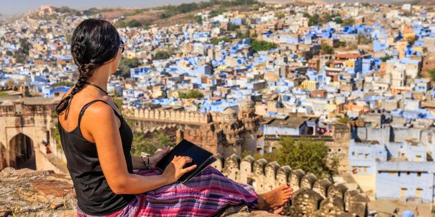Young female tourist using digital tablet. The blue city of Jodhpur on the background. Jodhpur is known...