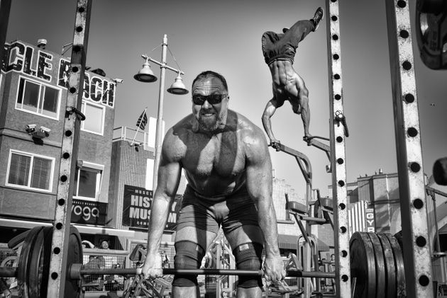 A weightlifter lifts a barbell loaded with heavy plates while a bodybuilder performs an aerial handstand...
