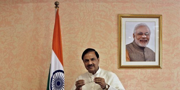 India's Culture Minister Mahesh Sharma, poses next to an Indian national flag and a portrait of India's...