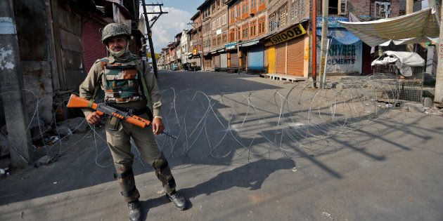 An Indian policeman stands guard in a deserted street during a curfew in Srinagar July 12, 2016. REUTERS/Danish