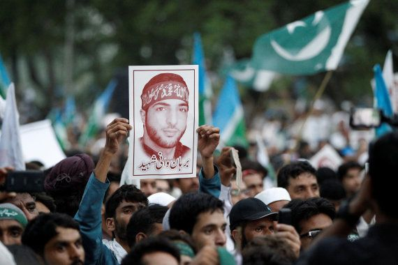 A picture of Hizbul Mujahideen commander Burhan Wani is held up during a rally condemning the violence...