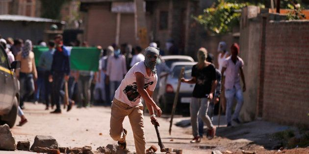 A demonstrator hurls a stone towards Indian police during a protest in Srinagar against the recent killings...