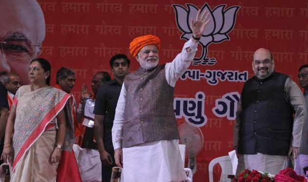 Prime Minister Narendra Modi waves during a reception accorded to him by Bharatiya Janata Party supporters...